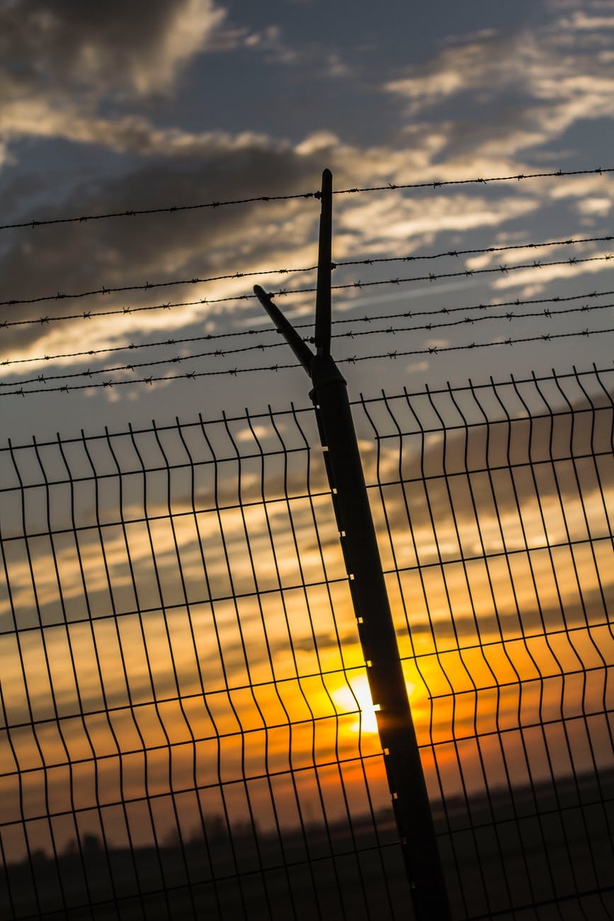 gray metal fence during sunset